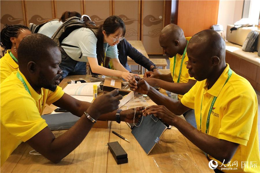 非洲青年代表在中国志愿者的帮助下体验制作线装书。