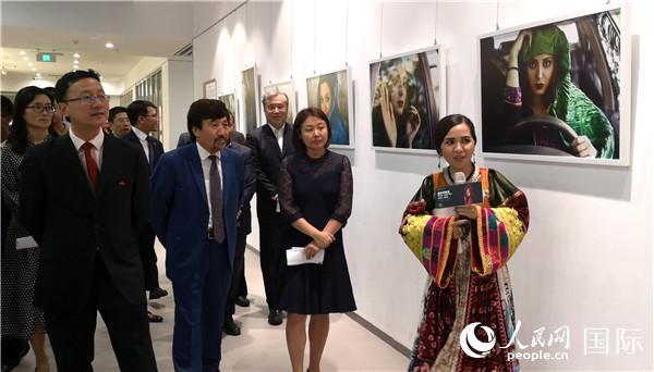 阿富汗女摄影师法蒂玛·侯赛因(右)向嘉宾介绍《战争中的美》展览作品。  人民网记者 李琰摄