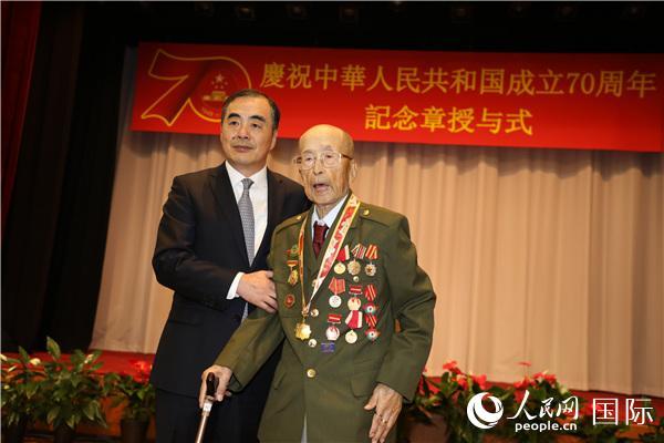 """中国驻日本大使孔铉佑与获颁""""庆祝中华人民共和国成立70周年""""纪念章的日本籍老战士合影。记者刘军国摄"""