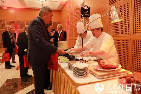 来宾们在招待会现场品尝北京烤鸭。郑琪 摄