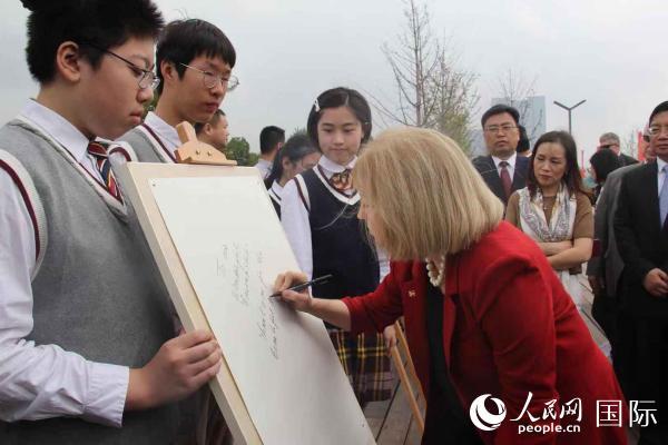 """克鲁森市长在南京市第五中学的""""我心中的圣路易斯""""书画展上,为学生们签名留言。她说,孩子们的画作让我们更加相信,两市的友谊将继续传承。刘歌摄"""