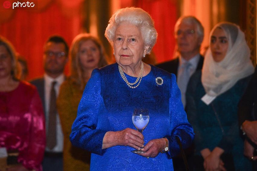 英国女王出席慈善活动 深蓝裙装手持高脚杯优雅华贵