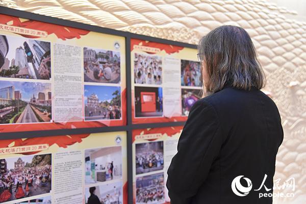 """嘉宾在观看""""庆祝澳门回归20周年""""图片展。刘玲玲摄"""