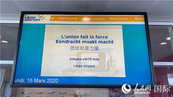 """列日机场大屏幕用三种文字打出""""团结就是力量""""。"""