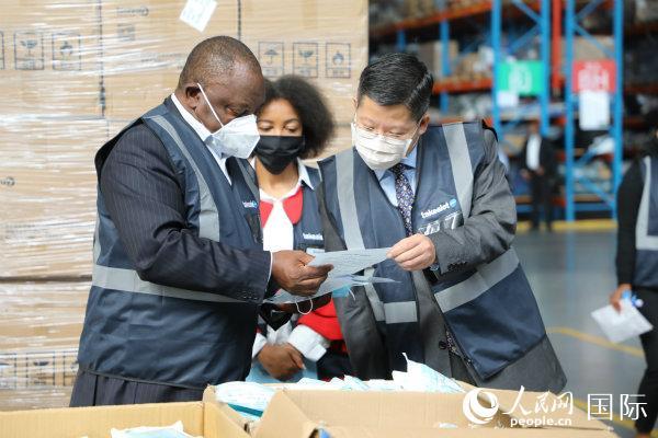 4月30日,南非全国传媒集团向南非政府交接从中国采购的第二批抗疫捐赠物资。图为南非拉马福萨、中国驻南非使馆临时代办李南在了解物资有关情况(吕强 摄)