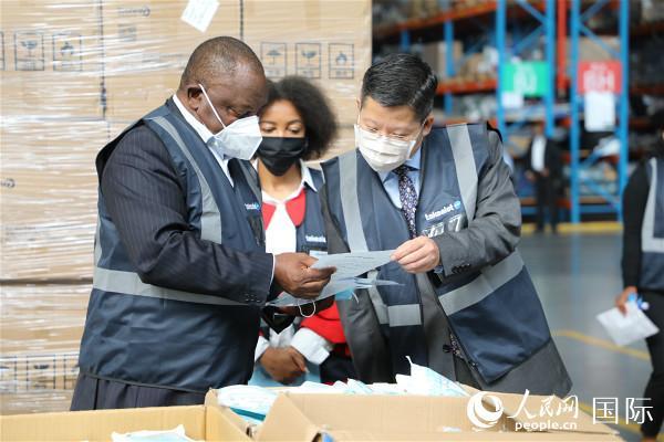 4月30日,南非总统拉马福萨接受南非全国传媒集团从中国采购的第二批抗疫物资,在中国驻南非使馆的协助和支持下,仅花费20多天时间就顺利运抵南非。左一为拉马福萨总统,右一为中国驻南非使馆临时代办李南。