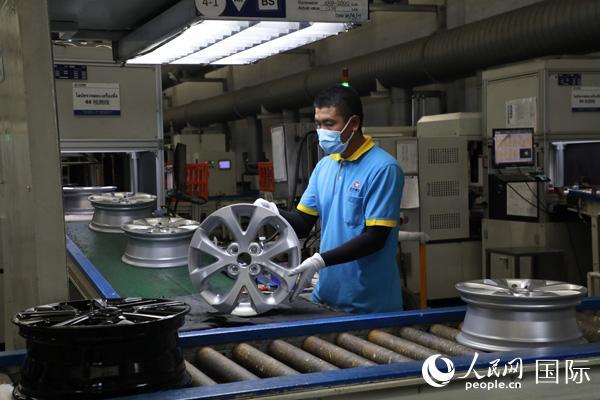 新泰车轮公司积极发展属地化,泰国员工达80%以上。图为泰籍员工在汽车轮胎生产线上工作。人民网记者孙广勇摄
