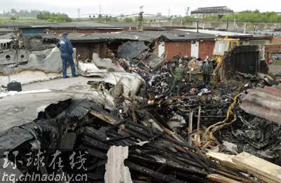 救援人员在飞机残骸附近寻找遇难者遗体.(路透社图片)
