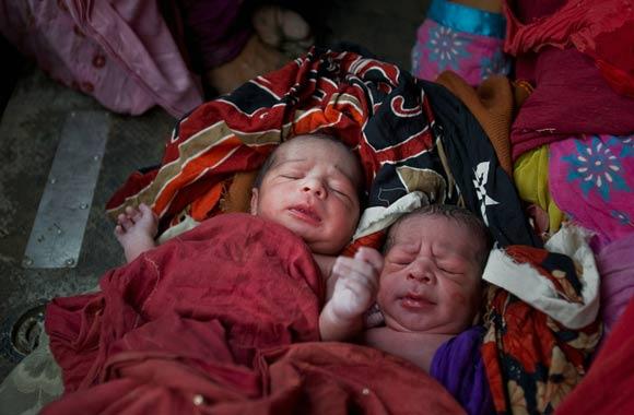 新生的双胞胎男孩躺在军用直升机上的一条毯子里