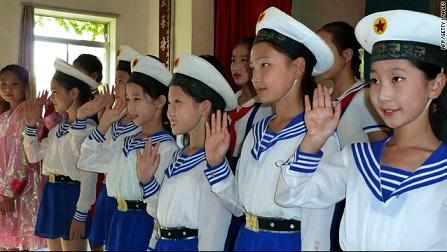 外国参观者参观一所平壤当地学校时,身穿海军制服的小姑娘们像来宾挥手。摄于9月23日。